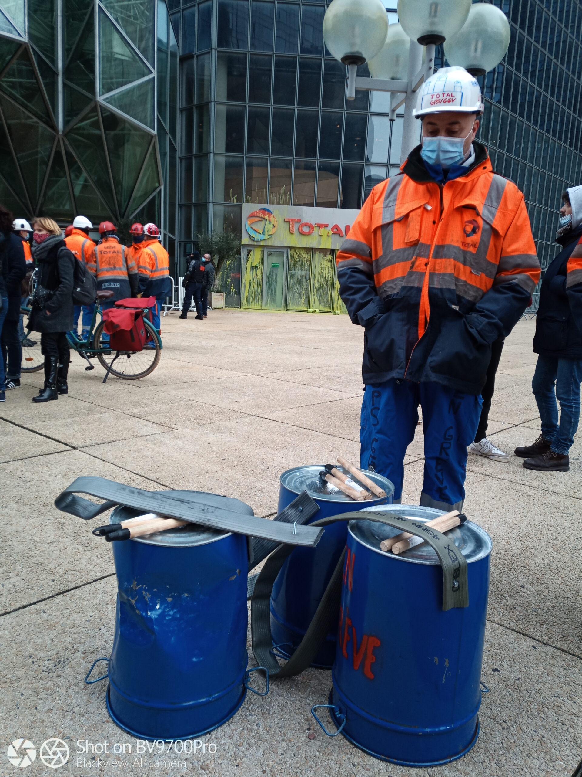 Salariés de la raffinerie Grandpuits au pied de la Tour total de la défense à Paris lors d'une action visant à dénoncer le greenwashing de l'entreprise.