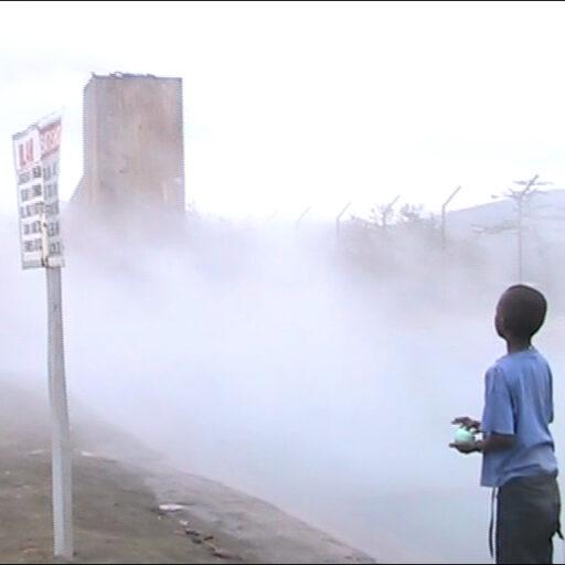 Simeon. Jeune enfant maasai jouant au football dans les nuages de vapeurs sulfurés de l'industrie géothermie (Olkaria, Kenya).